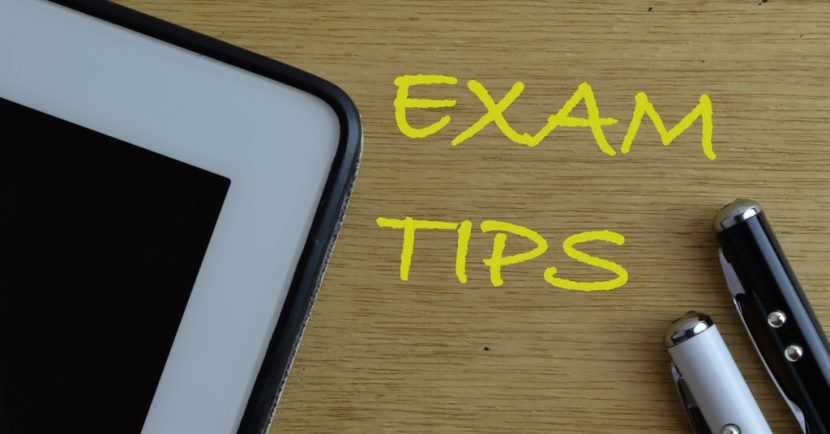 """Top view of tablet and pens with """"Exam Tips"""" on wooden background"""